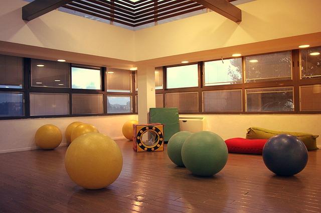 屋内施設に、大小様々なジムボールやマットなどが置かれている風景