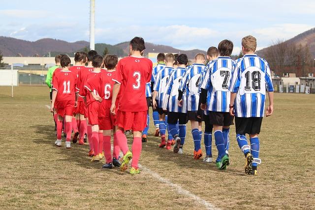 サッカーの試合で両チームの選手が縦に並びながら入場するシーン