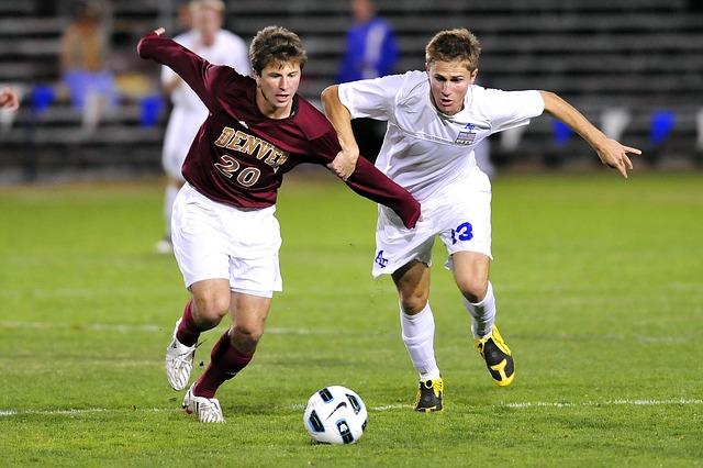 サッカーの試合で2人の選手が手で相手を遮りながらボールを奪い合っている風景