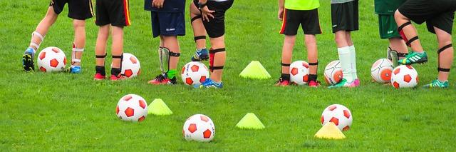大勢のサッカー少年の足元とボールやマーカーをズームアップした風景