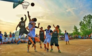屋外でバスケットボールの試合をしている風景