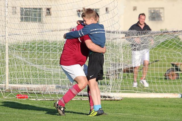 横に倒れているサッカーゴールの前で大人の男性と少年が抱き合っている風景