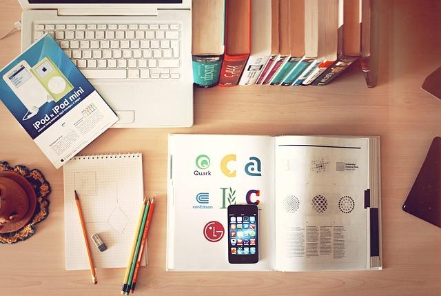 机の上にパソコン、テキスト、ノート、スマホ、鉛筆が置かれている