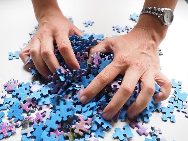 たくさんのパズルのピースを両手で掴んでいる風景