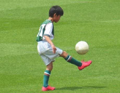 少年が芝の上でインステップのリフティングをしている風景