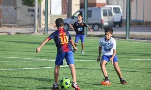 バルセロナのメッシのユニフォームを着た少年が、ドリブルでディフェンダーに向かっている様子