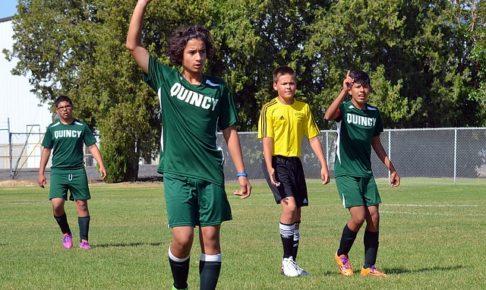 中学生年代のサッカーの試合風景で緑のユニフォームを着た選手が手を上げてアピールしている