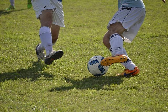 サッカーの試合で、オフェンスの選手がディフェンダーをドリブルでかわそうとしている場面の下半身をズームアップした風景