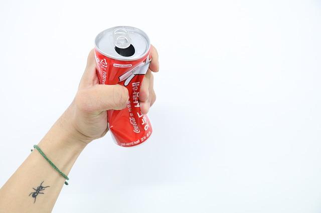 赤い炭酸飲料の空き缶を手で握りつぶしている画像