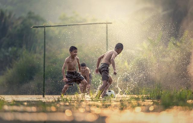 河原で男の子たち3人が上半身裸になってサッカーをして遊んでいる様子