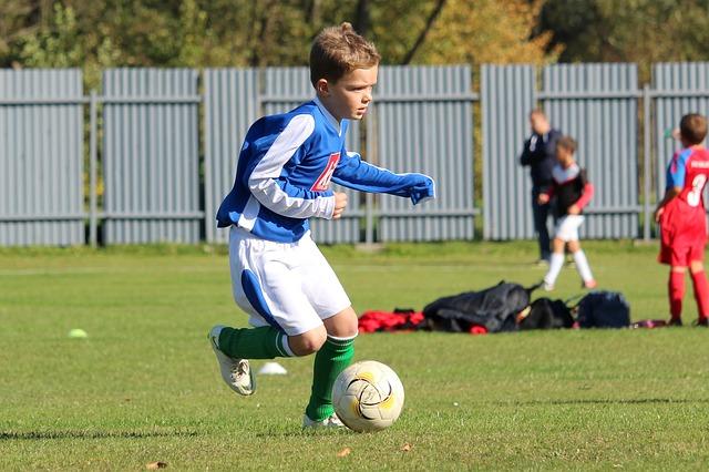 少年サッカーの試合で1人の選手がドリブルをしている姿を映した風景