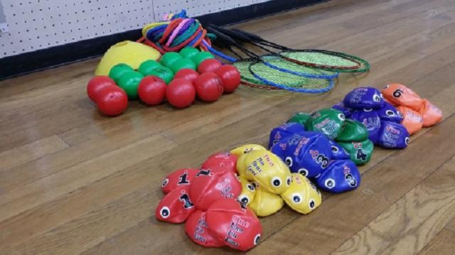 床に並べたビーンバッグ6色・ソフトボール2色・マーカー・縄・バドミントンラケット