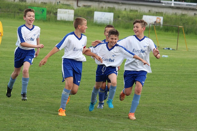 少年サッカーの試合でゴールを決めて味方選手と喜びを分かち合う場面