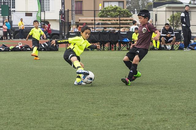 少年サッカーの試合でオフェンスの選手がディフェンダーをインサイドの切り返しでかわそうとしている風景