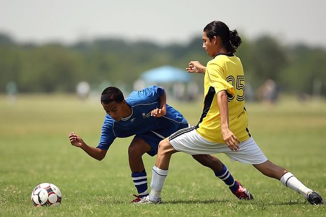 サッカーの1対1で相手をかわす際にオフェンス側が態勢を崩している場面