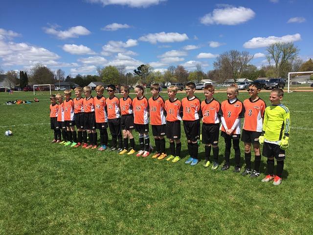 16人のサッカー少年少女が横一列に並んでいる風景