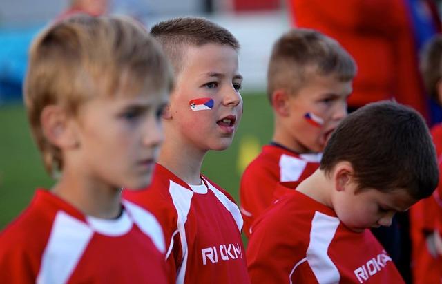試合に出場していない4人の少年たちがコートの外から試合の行方を見守る風景