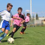 少年サッカーの試合でディフェンダーを振り切ってボールを蹴ろうとしている場面