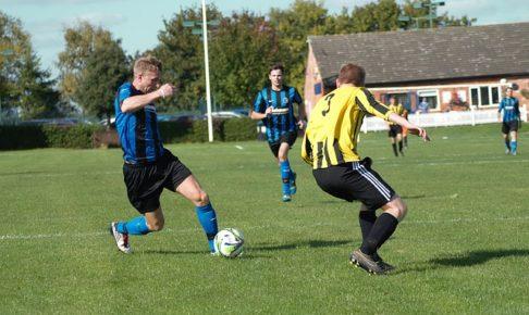 サッカーの試合でオフェンスの選手がディフェンダーをかわして抜き去る場面