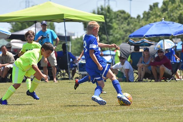 サッカー少年の試合で、オフェンスの選手がディフェンダーに背を向けながらターンをしようとしている風景