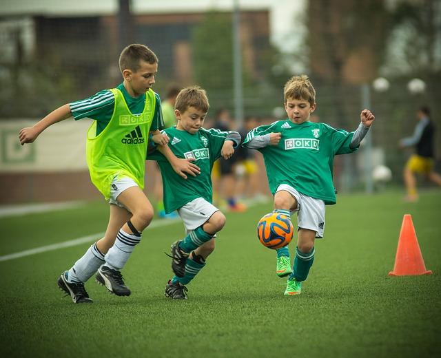 サッカー少年3人がボールに集中して奪い合う風景