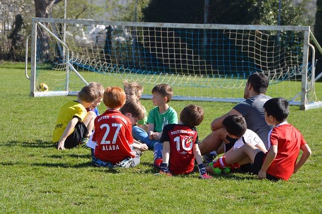 幼い子供たちがコーチの周りに集まって座りながら談笑している風景