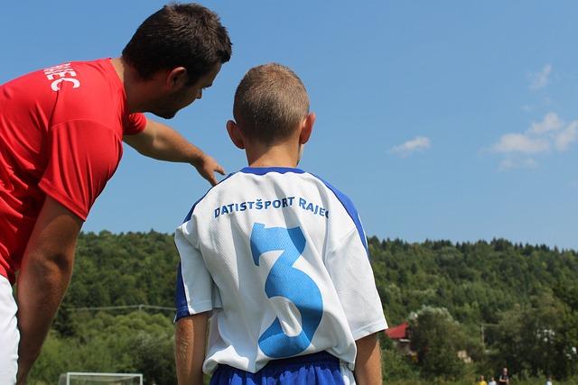 サッカーの指導者が、少年サッカーで1人の選手に手をかざしながら指示をしている様子を後方から映している場面