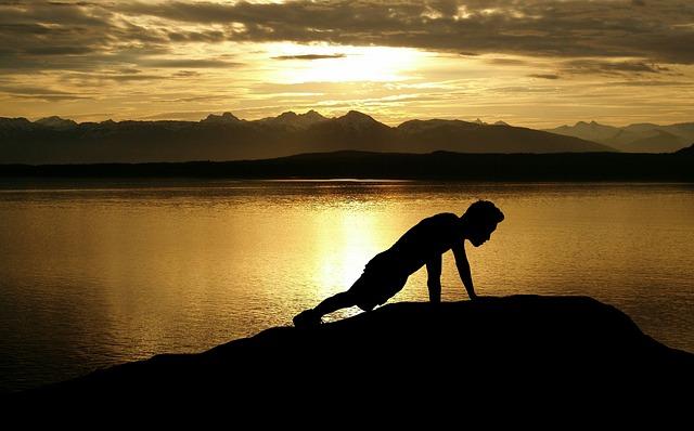 逆光が湖に反射している所で腕立て伏せをする男性のシルエット
