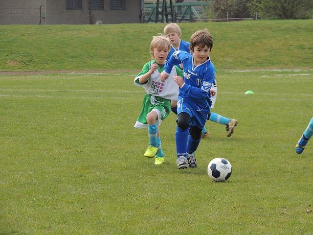 身体の大きい子供のサッカー選手がドリブルで小柄な相手選手をドリブルで抜き去る場面