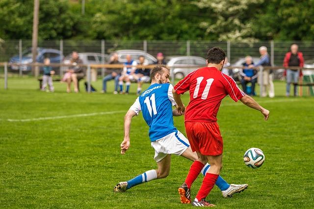 大人のサッカーの試合で、足を出して相手のボールを奪う場面