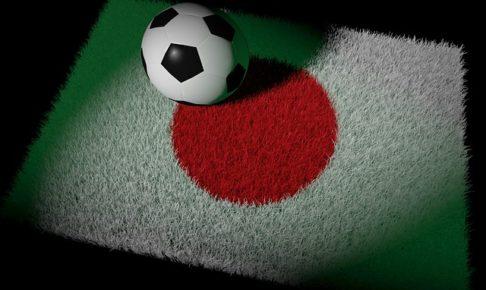 日本の国旗をイメージした芝の上にサッカーボールが置かれているイラスト