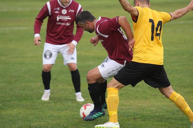成人サッカーの試合で、ディフェンスの選手がオフェンスの選手に身体を押し付けている風景