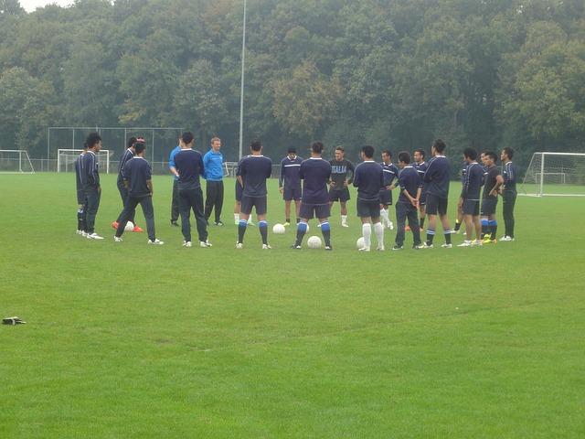 サッカー選手たちがコーチの話を聞く為に輪になっている風景