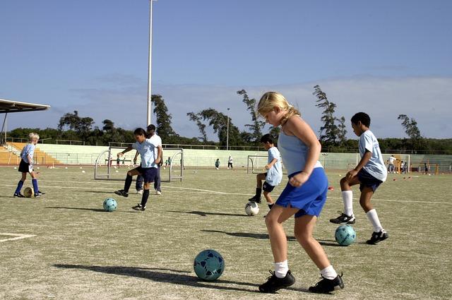 熱心にサッカーのトレーニングをしている少女と少年の風景