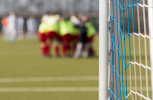 サッカーのゴールポストがズームアップされていて、コート内でサッカー選手が輪になっている風景