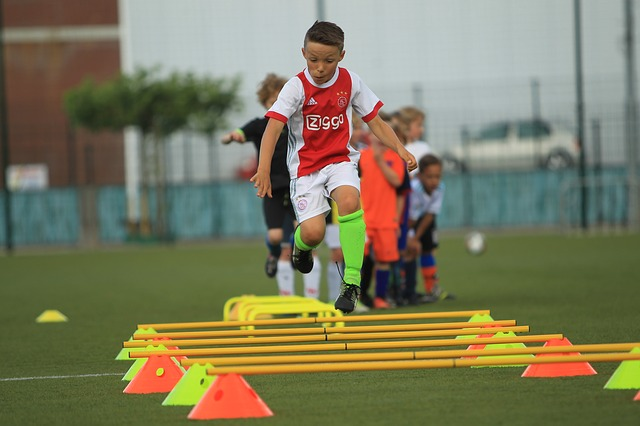 白と赤のデザインをしたサッカーのユニフォームを着た少年がミニハードルをジャンプしている風景