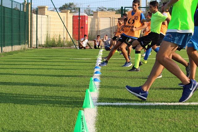サッカーコートのタッチラインにマーカーなどが置かれ、大勢の選手たちが反復して走り込みをしている風景