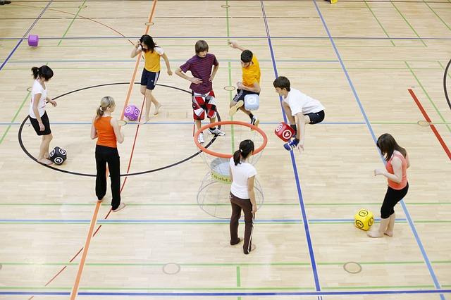 体育館で子供たちに様々な道具を使ってエクササイズの指導をしている風景