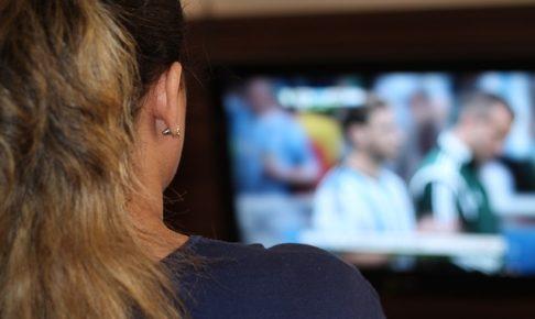 サッカーのテレビ観戦をしている女性を後方からズームアップした風景