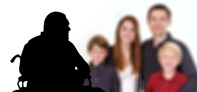 車椅子に乗った老人のシルエットと、その背後に4人の家族がぼやけて見えている画像
