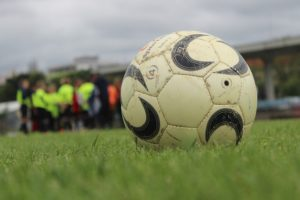 芝生の上に置かれたサッカーボールと、背後にサッカー選手がぼやけて見える風景