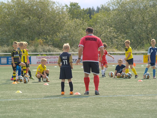 大勢の子供たちがいる中で個人的にコーチからサッカーの指導を受けている場面