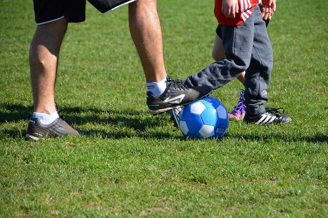 父親がサッカーボールに右足を乗せ、隣に子供がいる下半身をズームアップした風景