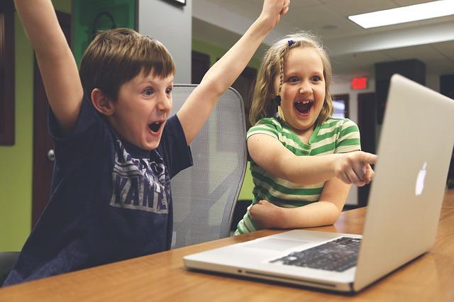 パソコンの画面を見て喜ぶ男の子と女の子