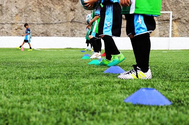 少年サッカーのトレーニングで、横に並んだ子供たちの足元とマーカーをズームアップした風景