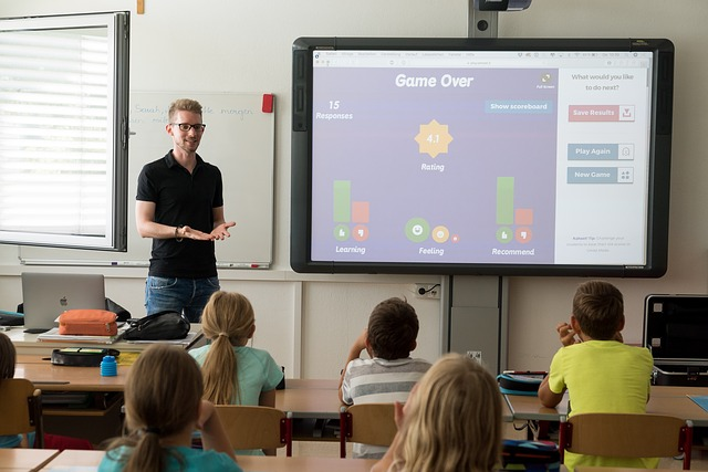 小学校でパソコンとプロジェクターを用いて授業を行っている風景