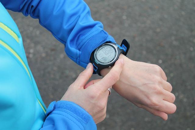 左手につけた時計を右手で操作している風景