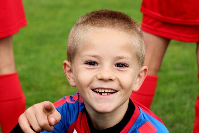 サッカーのユニフォームを着た子共が、こちら側に指をさして笑っている画像