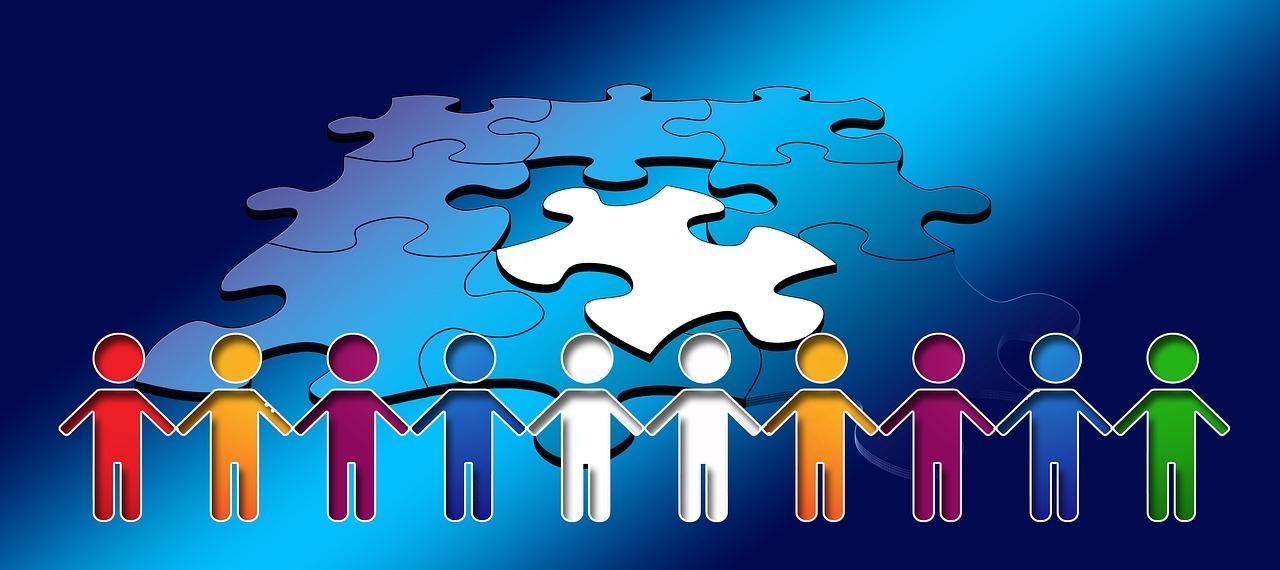 色とりどりの人間が横に並んで手を繋ぐ、その背景にパズルがあるイラスト