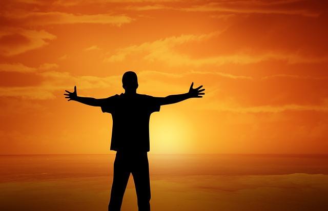 夕日に向かって両手を広げて立つ男性の姿
